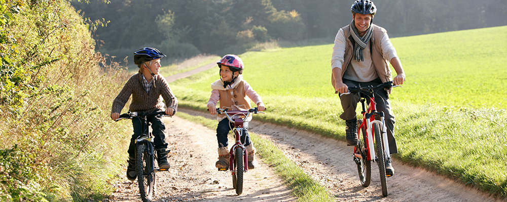 Two children and a man biking on the country side